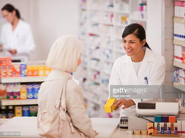 Farmacêutico dar medicação ao cliente em loja de Drogas