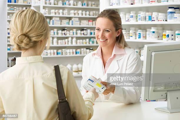 pharmacist handing woman medication - ショルダーバッグ ストックフォトと画像