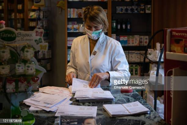 A pharmacist handles some prescriptions on March 11 2020 in Milan Italy The Italian Government has strengthened up its quarantine rules shutting all...