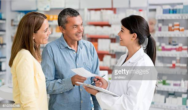 Pharmacist helping couple at a drugstore
