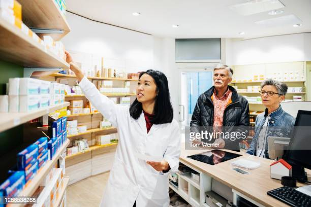 pharmacist helping customers with drug prescription - black hair stock pictures, royalty-free photos & images