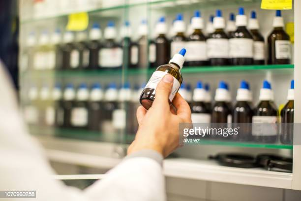 pharmacist holding a medicine bottle in hand - homeopathic medicine stock photos and pictures