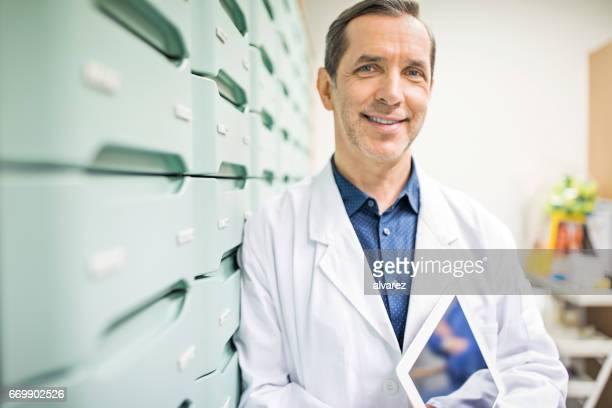 pharmacist holding digital tablet in storage room - bata de laboratório imagens e fotografias de stock