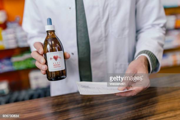 Pharmacist holding flask and prescription in pharmacy