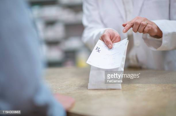 pharmacist holding out a packaged prescription stock photo - prescription stock pictures, royalty-free photos & images