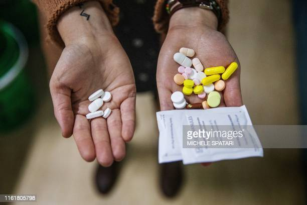 A pharmacist holds two sets of pills in her hands showing the difference between the amount of tablets a patient takes on the new NIX course versus...