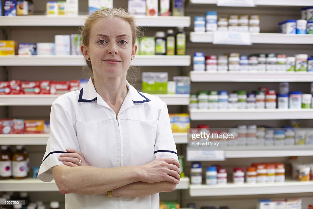 Pharmacist in her shop : Stock Photo