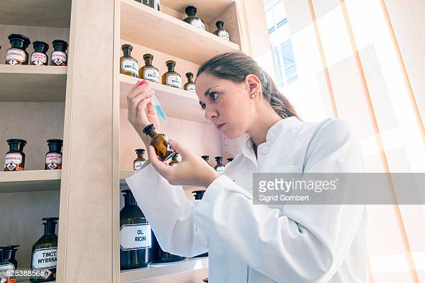 pharmacist in pharmacy, examining test tube contents - sigrid gombert stock-fotos und bilder