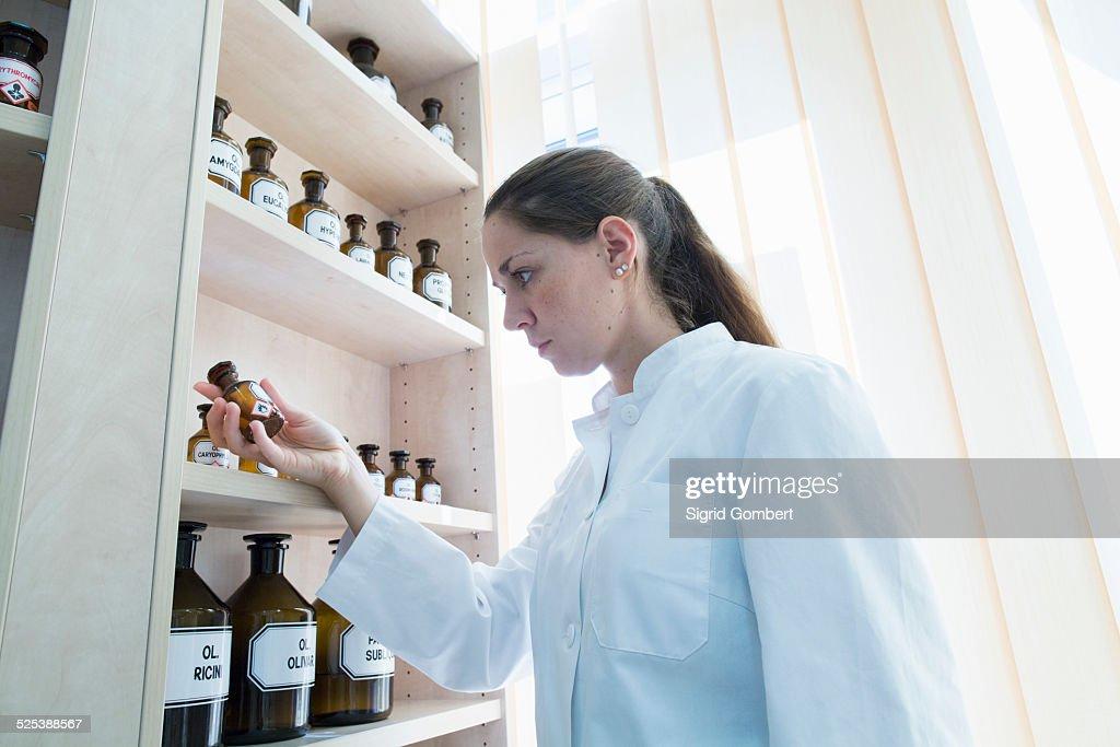 Pharmacist in pharmacy holding medicine bottle : Stock-Foto
