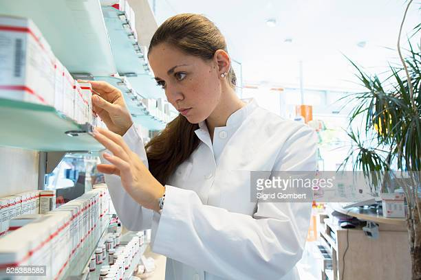pharmacist in pharmacy looking at medicine box - sigrid gombert stock pictures, royalty-free photos & images