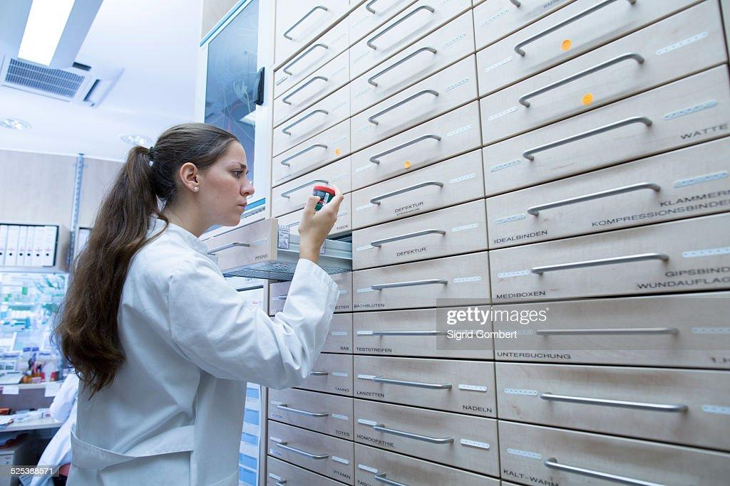 Pharmacist in pharmacy opening medicine file drawer : Stock-Foto