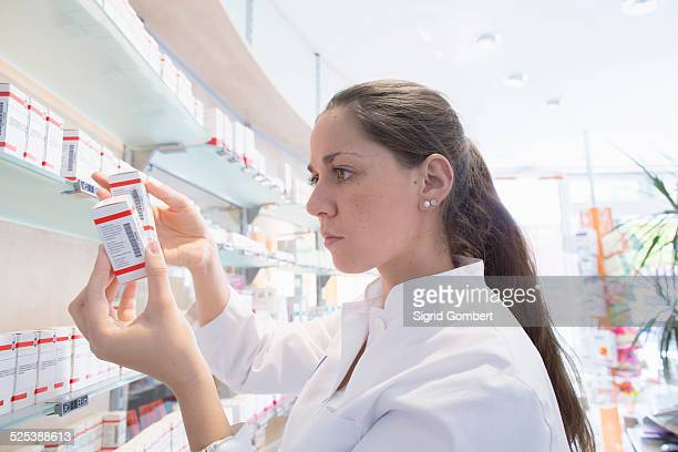 pharmacist in pharmacy reading medicine box - sigrid gombert stock pictures, royalty-free photos & images