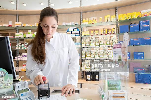 pharmacist in pharmacy stamping prescription - sigrid gombert stock-fotos und bilder