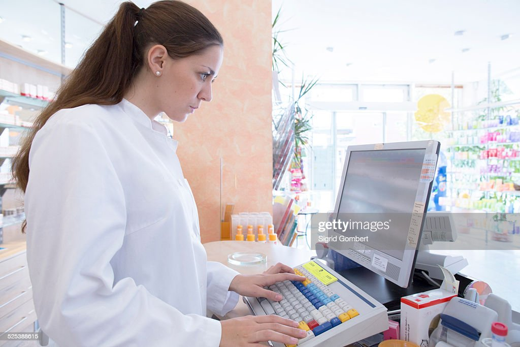 Pharmacist in pharmacy using computer : Stock-Foto