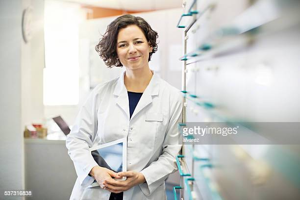 pharmacist leaning to a medicine shelf with digital tablet - medicijnen stockfoto's en -beelden