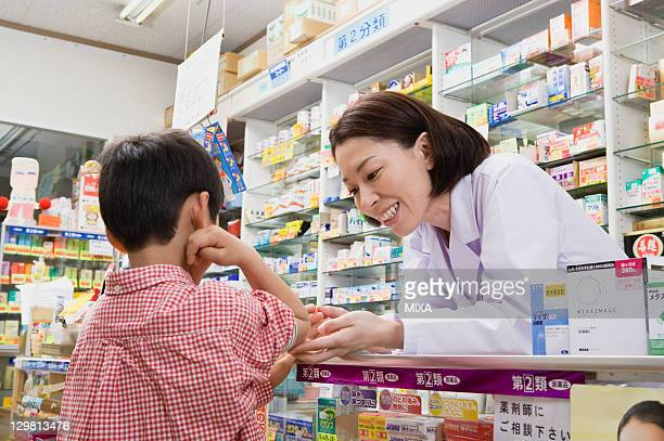 Pharmacist Looking Over Boy's Elbow