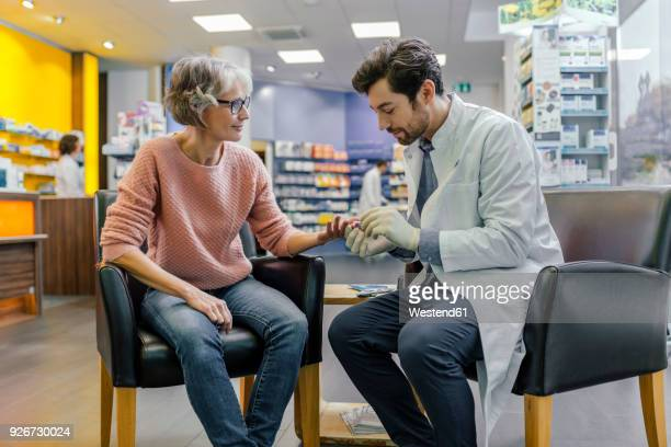 Pharmacist measuring blood sugar of customer in pharmacy