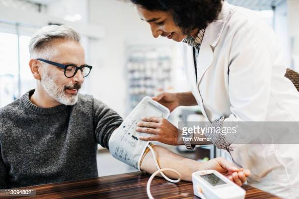 pharmacist measuring mature man's blood pressure - medicijnen stockfoto's en -beelden