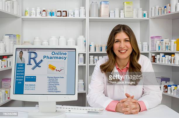 Pharmacist next to a computer displaying online pharmacy information