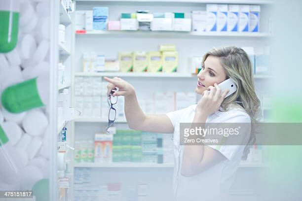 Pharmacist on phonecall and pointing to medication