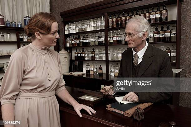 pharmacist receiving payment for medicines - newhealth stock pictures, royalty-free photos & images