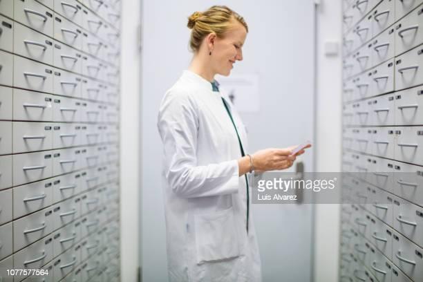 pharmacist searching prescribed medicine at storage room - lagerraum stock-fotos und bilder