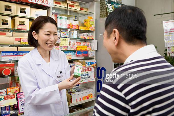 Pharmacist Showing a Box of Medicine to Customer