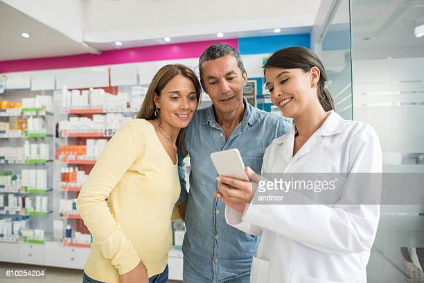 Pharmacist showing app to customers at a drugstore