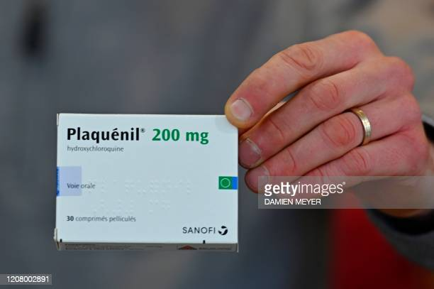 A pharmacist shows a box of antimalarial tablets called Plaquenil on March 23 in Rennes western France on the seventh day of a strict lockdown in...