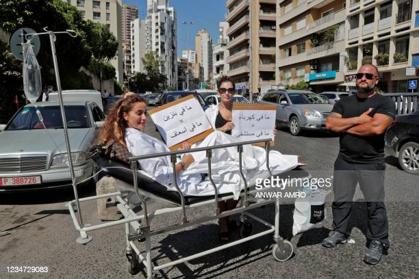 """Pharmacist sits on a stretcher holding a sign reading in Arabic """"no gasoline = no ambulance"""" while another stands by holding another sign reading """"no..."""