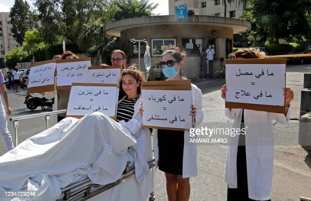 """Pharmacist sits on a stretcher holding a sign reading in Arabic """"no gasoline = no ambulance"""" while others stand by holding signs reading """"no..."""