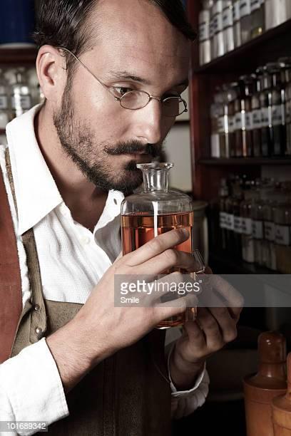 Pharmacist smelling a bottle