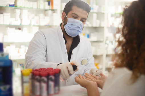 pharmacist squeezes hand sanitizer to the customer 1213070451