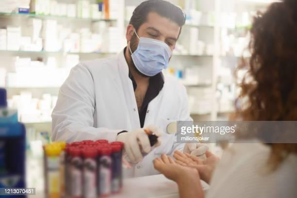 apotheker drückt handdesinfektionsmittel an den kunden - apotheke stock-fotos und bilder
