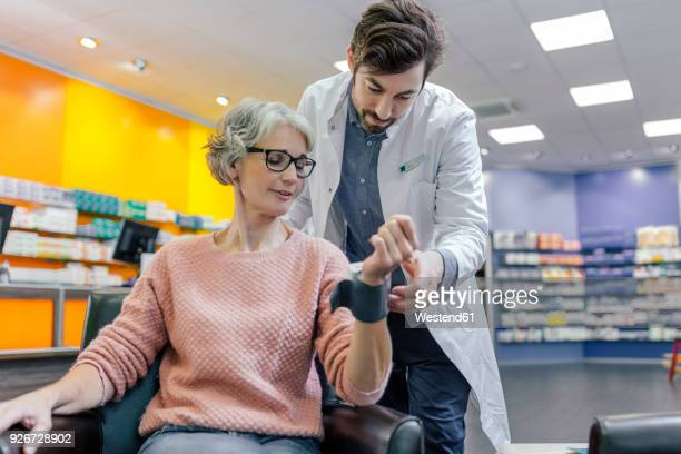 Pharmacist taking blood pressure of customer in pharmacy