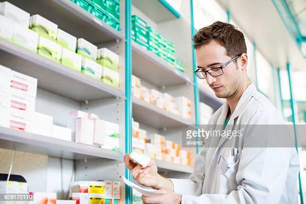 Apotheker mit Verschreibungspflichtiges Medikament aus Regal
