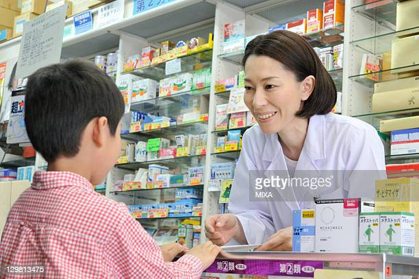 Pharmacist Talking to Boy at Drugstore