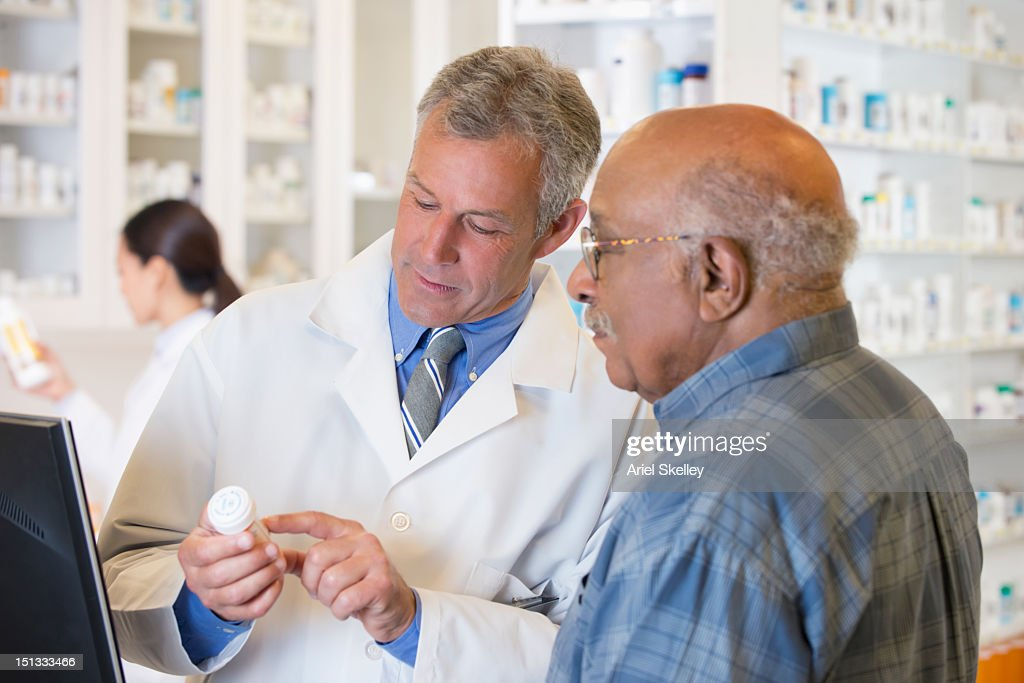 Pharmacist talking to customer about prescription : Stock Photo