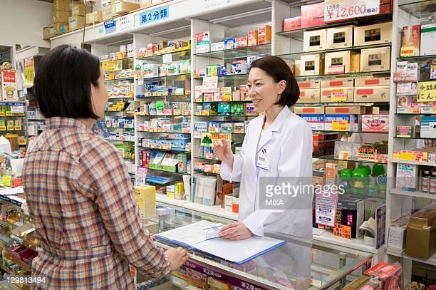 pharmacist talking to customer - 薬剤師 ストックフォトと画像
