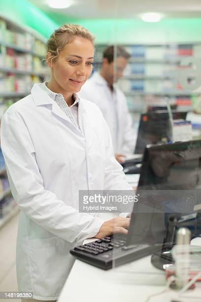Farmacéutico usando el ordenador en contador