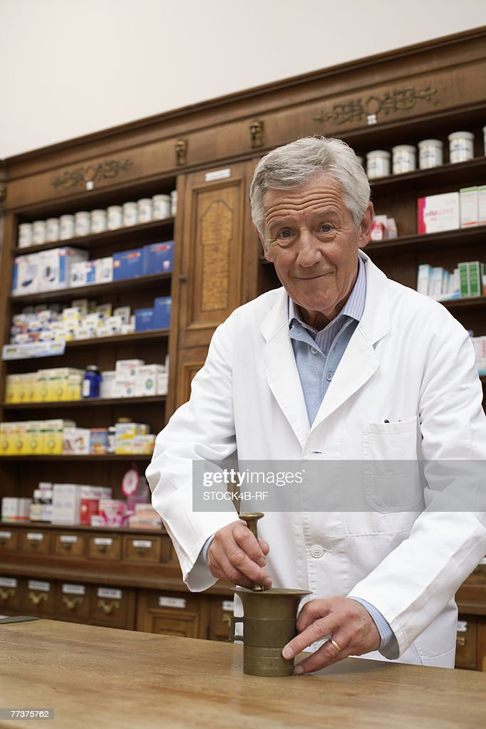 Pharmacist using pestle and mortar : Photo
