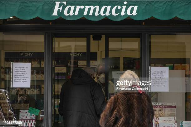 A pharmacist wearing a respiratory mask serves customers on February 23 2020 in Casalpusterlengo southwest Milan Italy Casalpusterlengo is one of the...