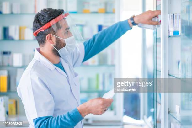 a pharmacist with a protective mask. giving the appropriate medicine. - helmet visor stock pictures, royalty-free photos & images