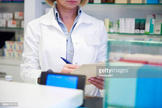 Pharmacist with clipboard checking stock in pharmacy