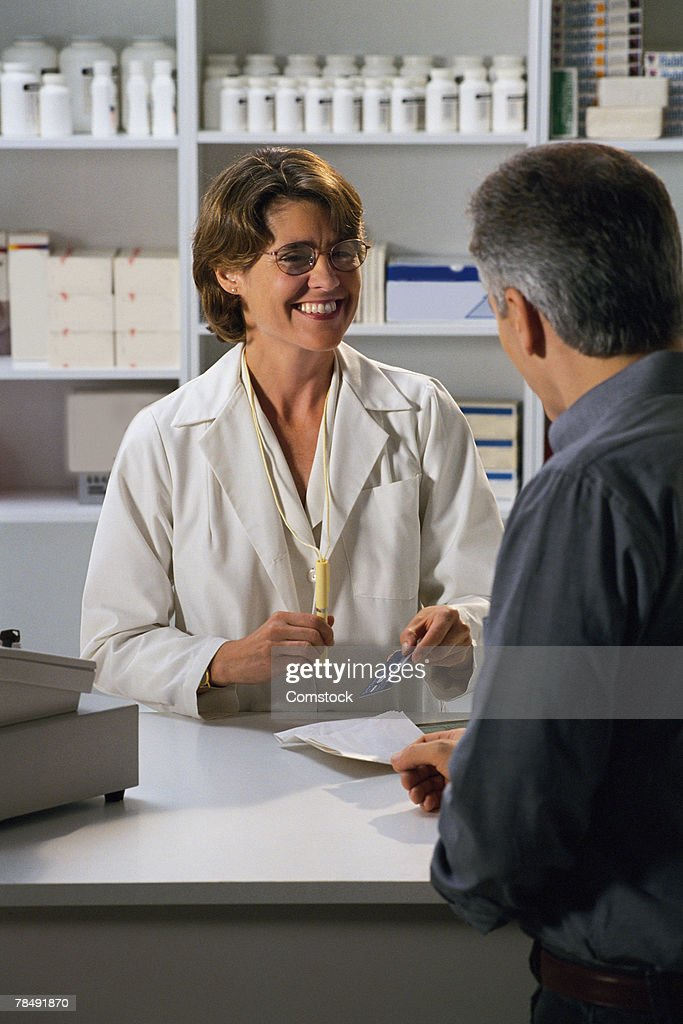 Pharmacist with customer : Stock Photo