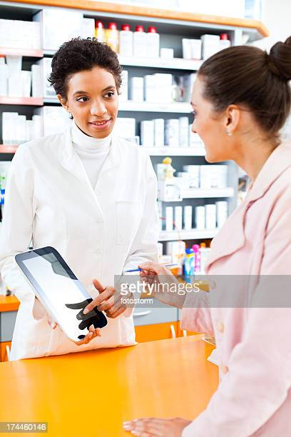 Pharmacist with digital tablet explaining instructions to customer in pharmacy