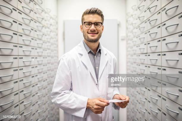 farmacéutico con prescripción de medicamentos en almacén - bata de laboratorio fotografías e imágenes de stock