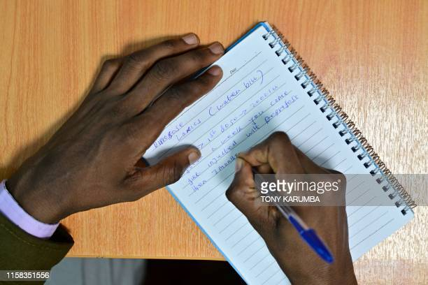 A pharmacist writes a doping regimen on a piece of paper as he gives an interview to AFP in Nairobi where he admits doping has become a common...