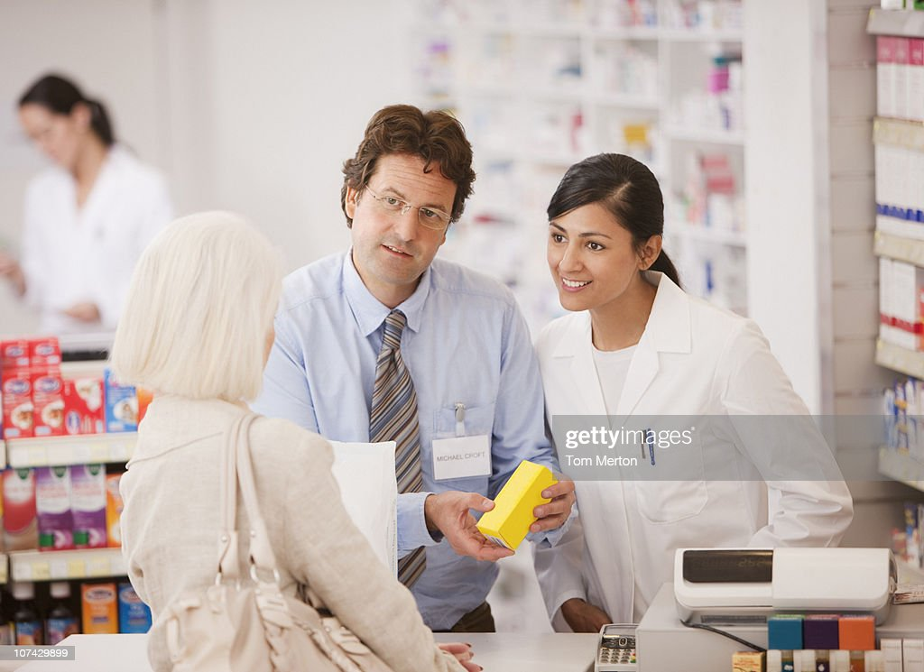 Pharmacists answering questions for customer in drug store : Bildbanksbilder
