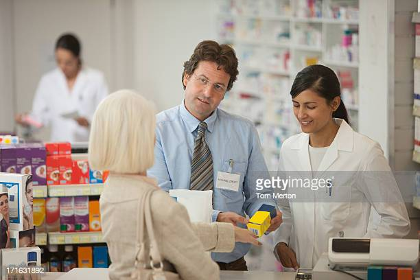 Pharmacists answering questions for customer in drug store